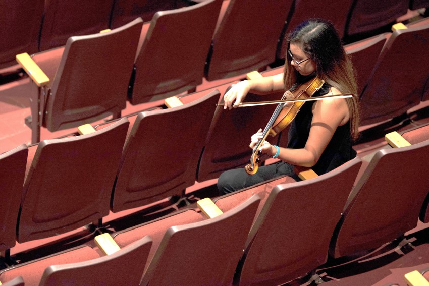 TWU student practices violin in the seats of Margo Jones performance hall