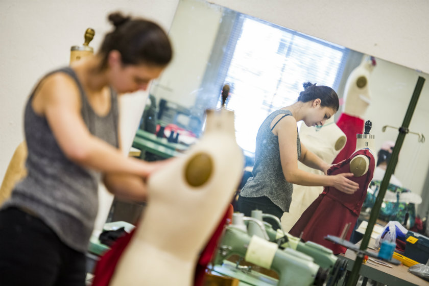 Photo of fashion student Oksana Bekh works on her dress for the annual Go Red for Women Fashion Show