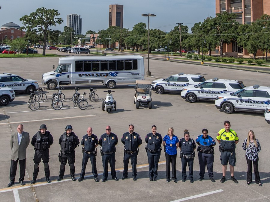 Members of police squad pose in front of police vehicles