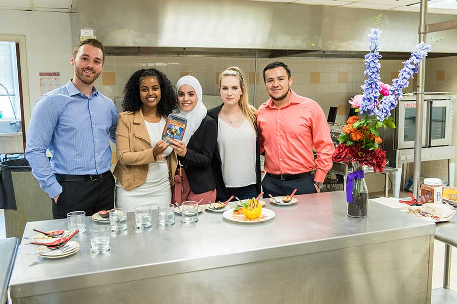 Five TWU students pose in an industrial kitchen setting with their Elote Bowls product prototype.