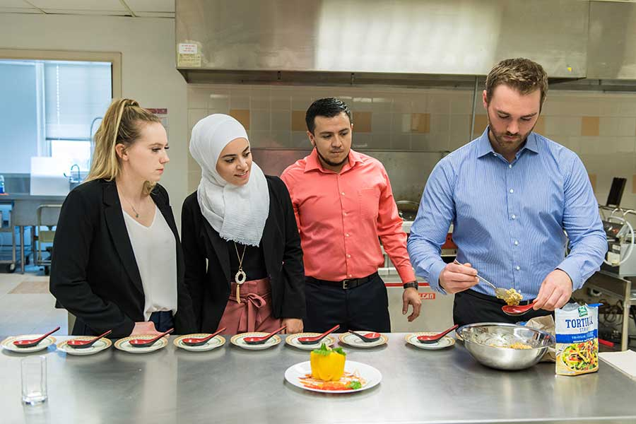 Five TWU students plate their elote food product in an industrial kitchen setting.