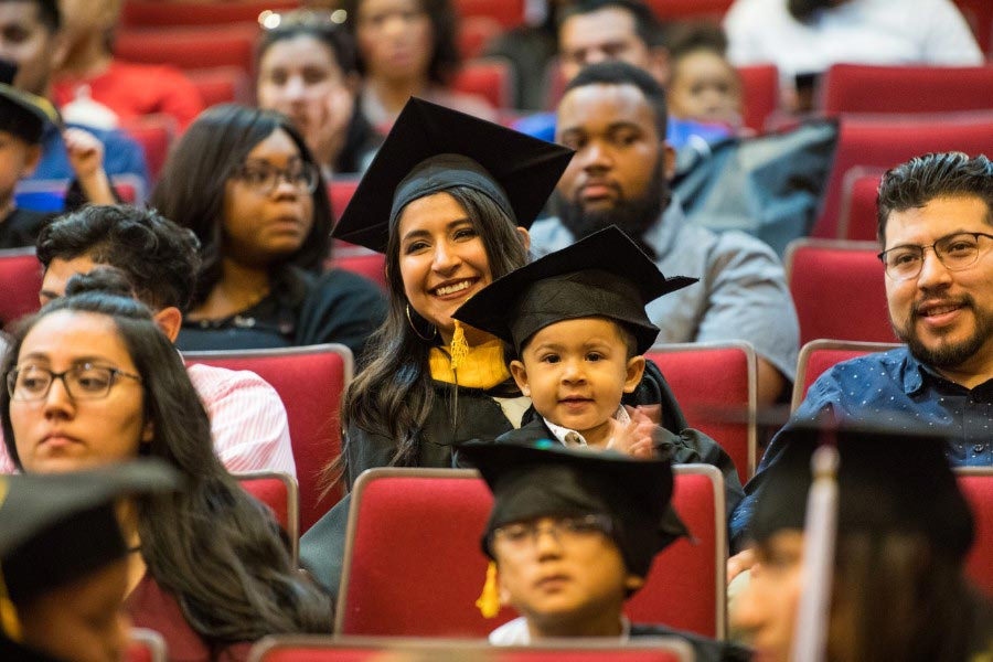 A TWU graduate in academic regalia with her son on her lap in a cap and gown.