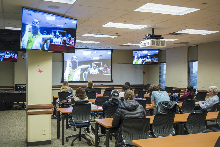 A classroom of TWU students watching as South African students on the TV screen shows them a meal.