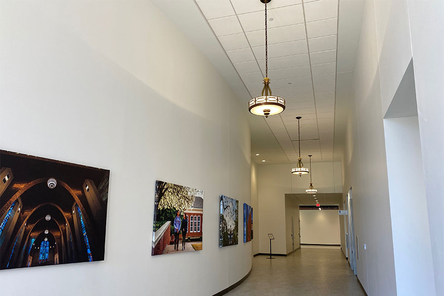 Vintage light fixtures hang down a modern hallway in TWU's renovated Hubbard Hall.