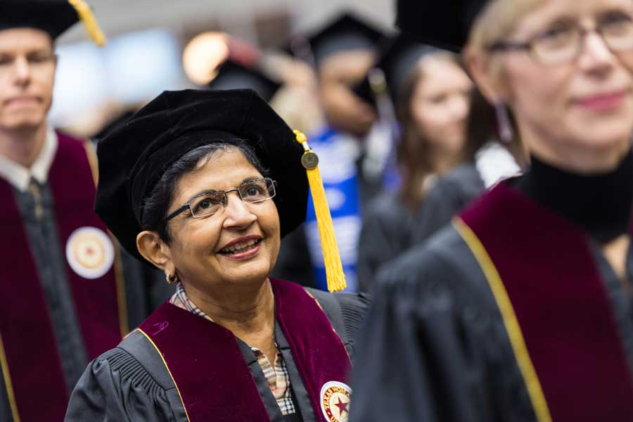 Kiran Kanwar walks in doctoral academic regalia during her commencement ceremony at TWU.