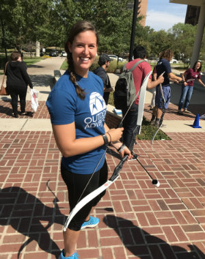 MacKenna Heath outside TWU's Fit & Rec center practicing archery.