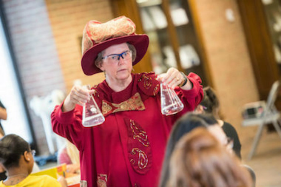 Doctor Cynthia Maguire dressed as a wizard while demonstrating chemistry principles to youngsters