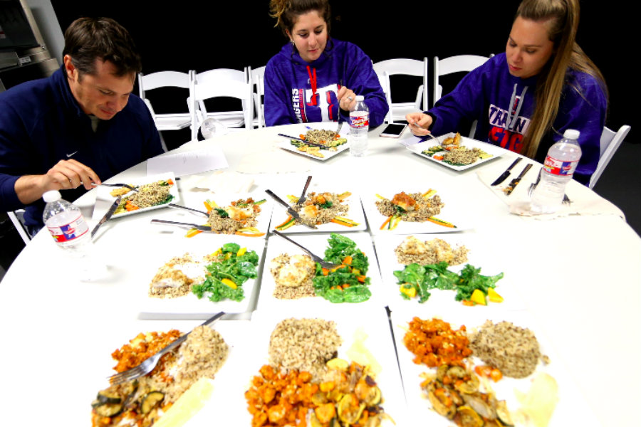 Lindsay Oar, Stephanie Fernandes and another coach sitting at a table filled with meals set to be judged by the three.
