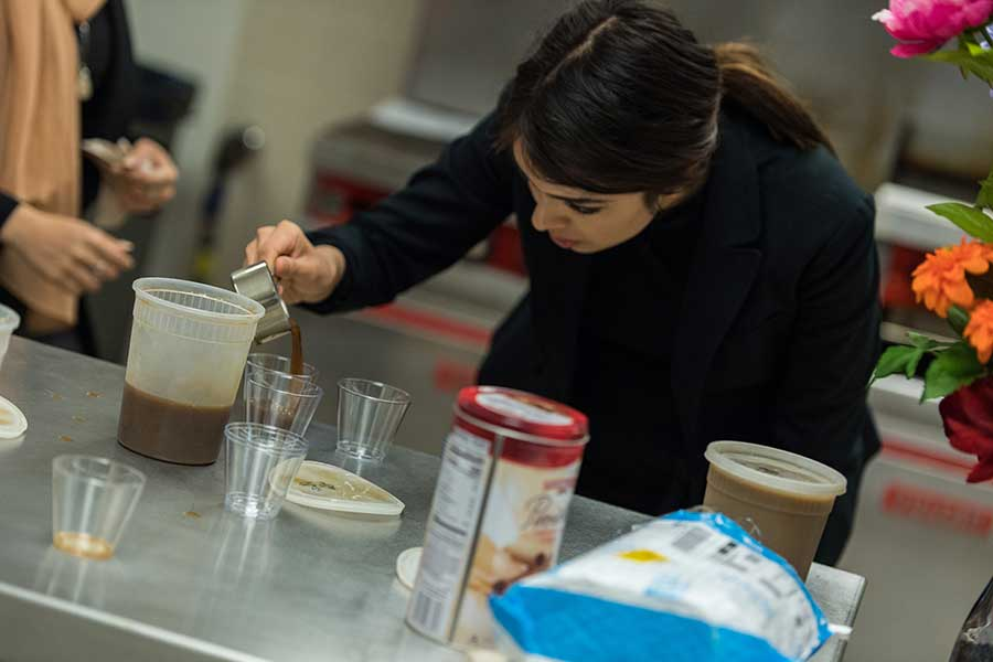 Shiraz Soltani plates her teams protein coffee product in an industrial kitchen setting.