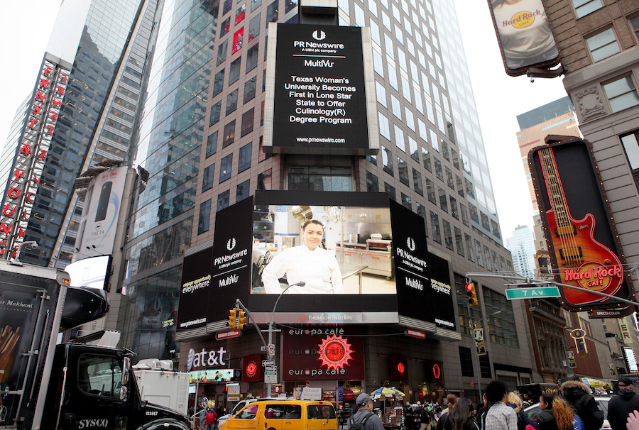 New York City Time Square buildings with large sign featuring smiling chef
