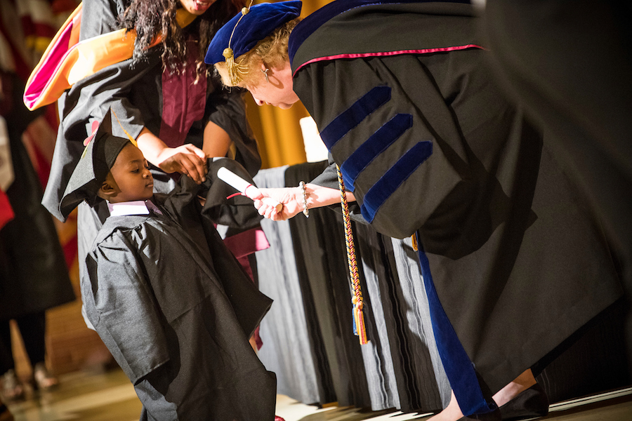 Small boy receives a diploma from TWU faculty member