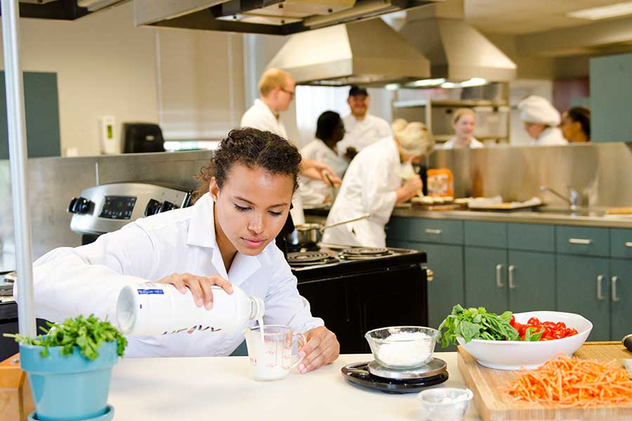 A TWU student measures milk into a cup while cooking in an industrial kitchen setting.