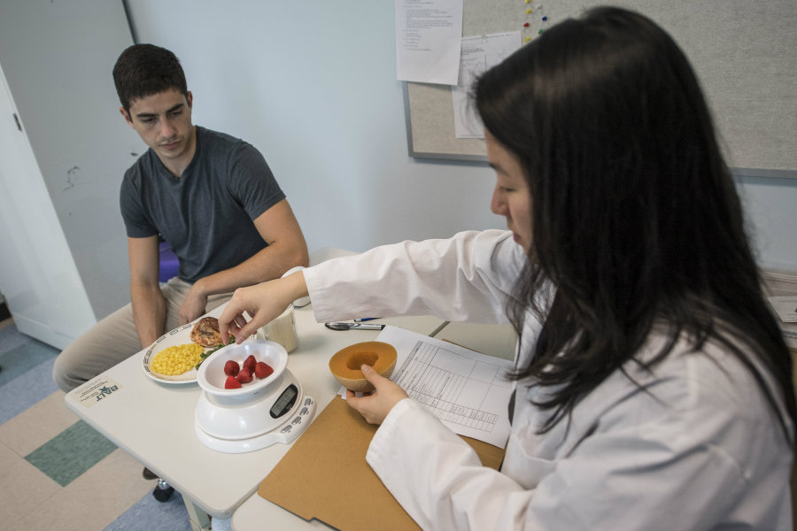 A woman in a lab coat weighing fruit and advising a man across from her on a healthy meal option.