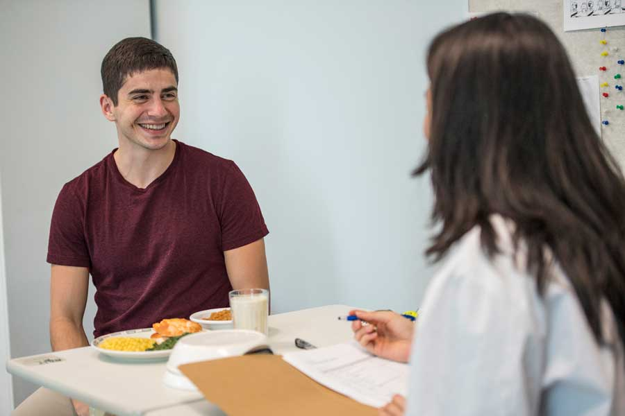 Female TWU dietitian talks to a male patient who has food options on table in front of him.