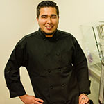 Walter Rivas in a chef uniform and posing in a kitchen setting.