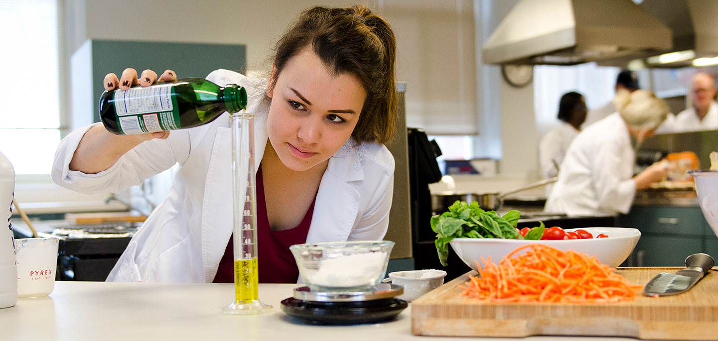 A culinology student measures olive oil into a narrow beaker