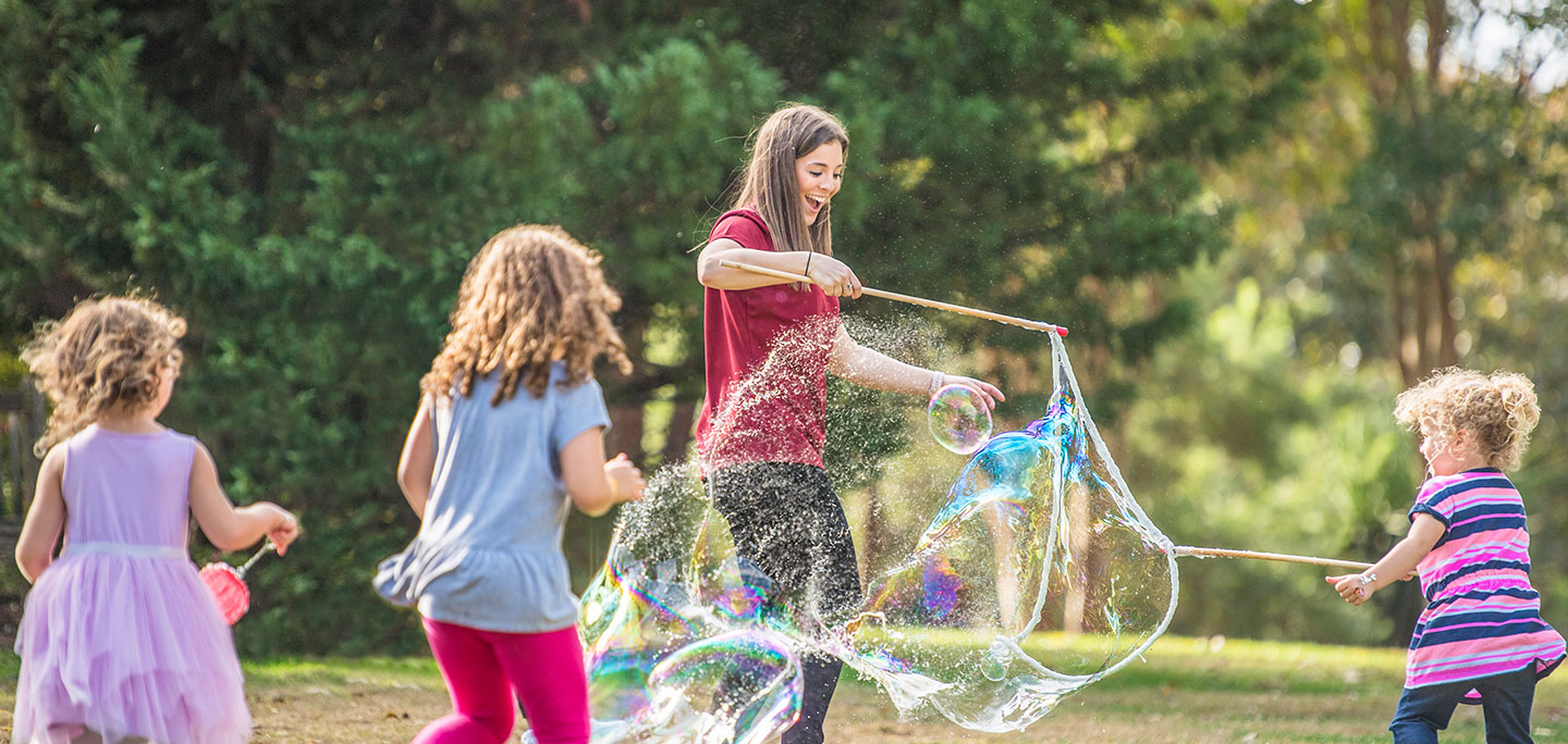 An occupational therapist uses bubbles to engage children on the autism spectrum in a natural environment