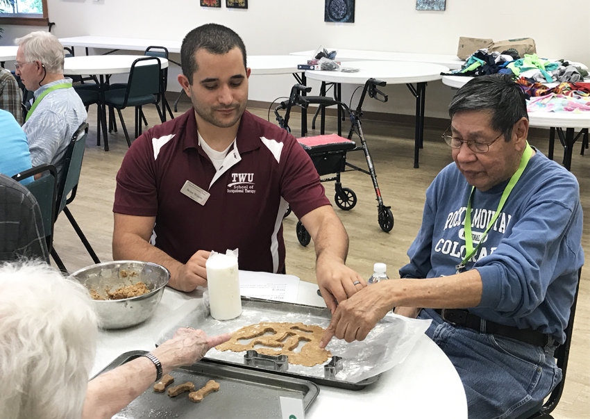 OT student works with adult patient on cookie cutter project