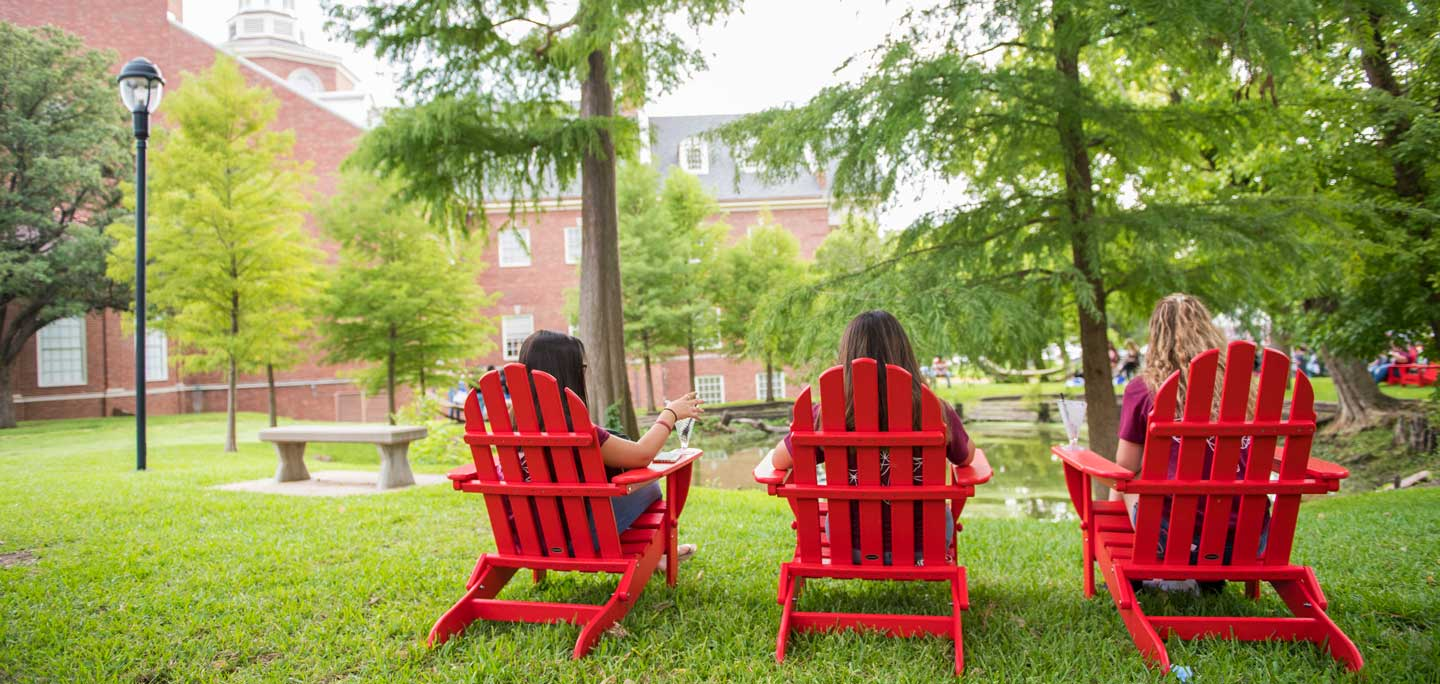Three students sit in lounge chairs outdoors on TWU's Denton campus.