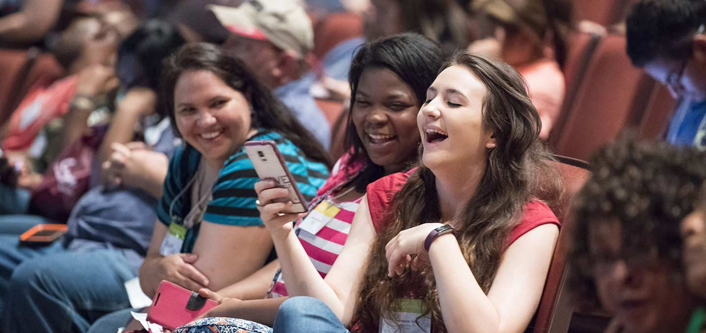 Three female students laughing at something one is sharing on her phone.