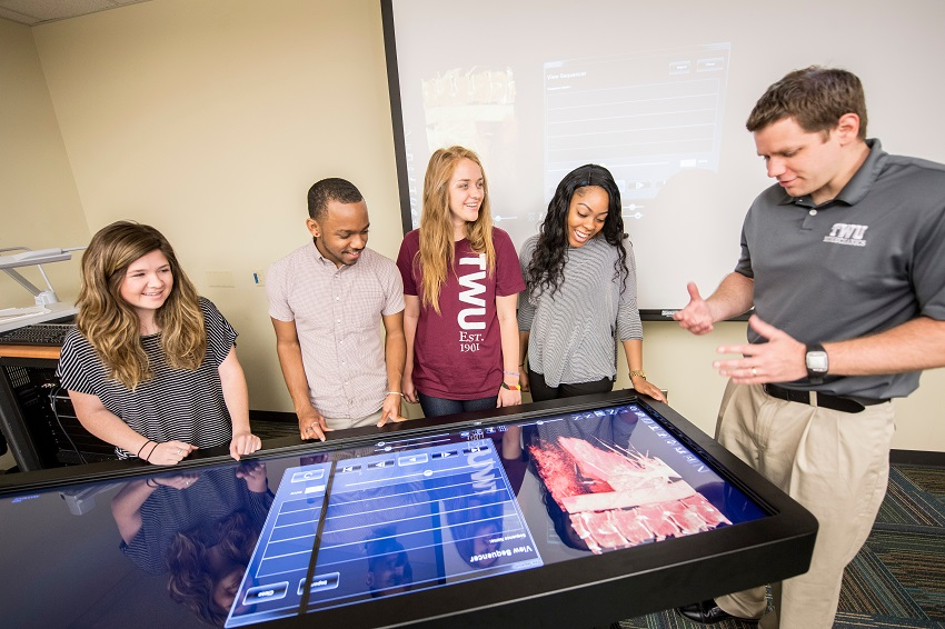 TWU students and an instructor gathered around a big screen table display