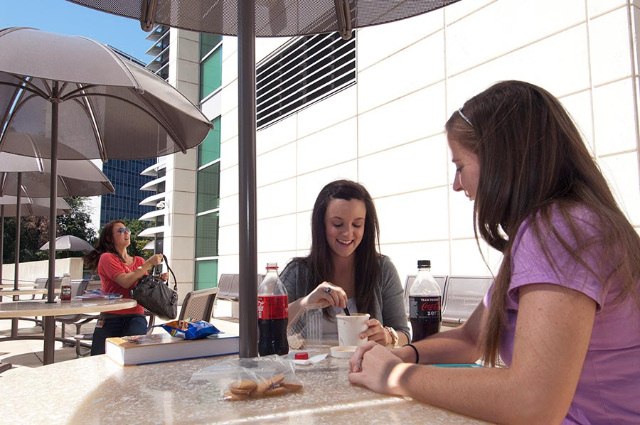TWU Houston students eat lunch outside on covered tables.