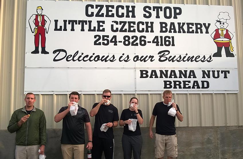 Five people standing in front of a sign for a Czechoslovakian bakery The Czech Stop, eating kolaches.