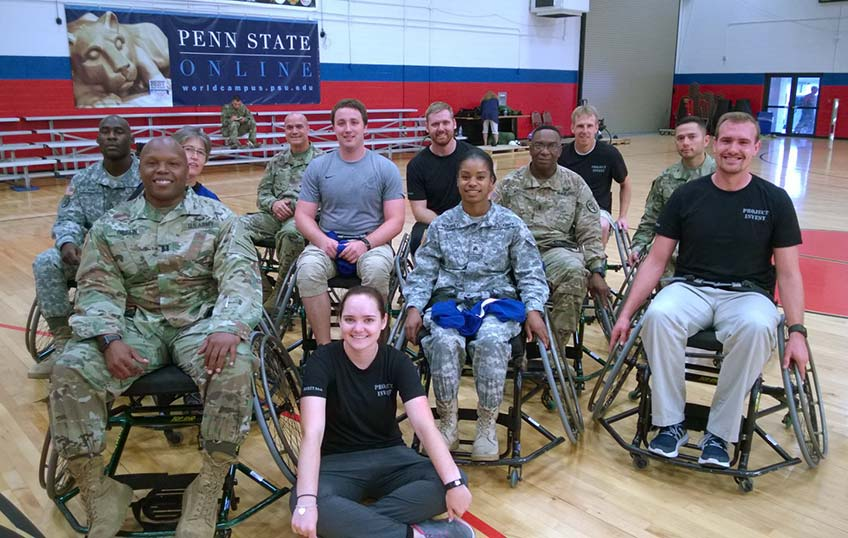 A group of young men and women in wheelchairs smiling at the camera. A young woman sits cross-legged on the floor in front of them.