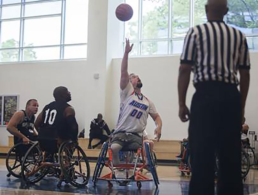 A man in a wheelchair raises his hand to catch a basketball as a referee watches.