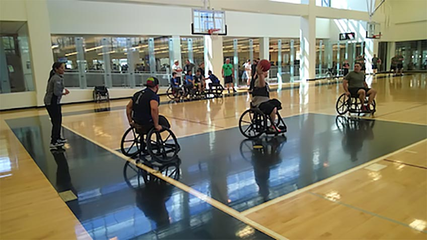 A group of people play basketball in wheelchairs