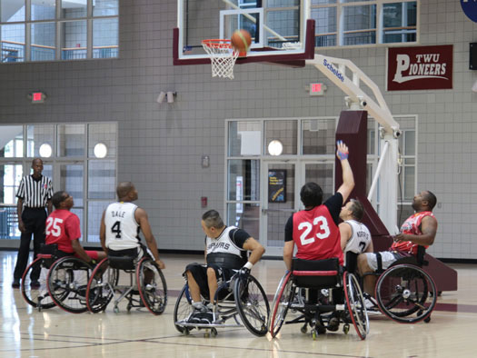 A group of people in wheelchairs play basketball together