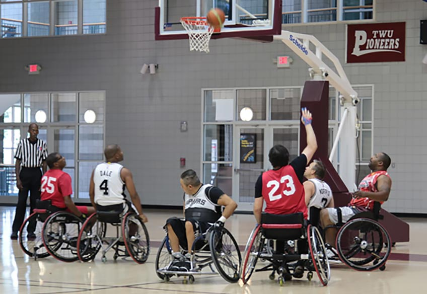 A group of people in wheelchairs playing basketball