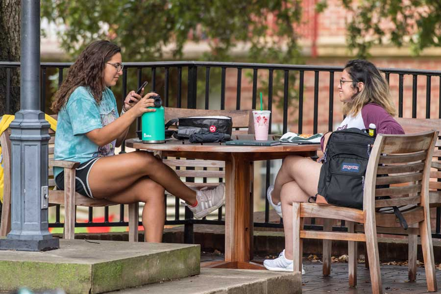 Two TWU students sit at a table outdoors and relax on the Denton campus.