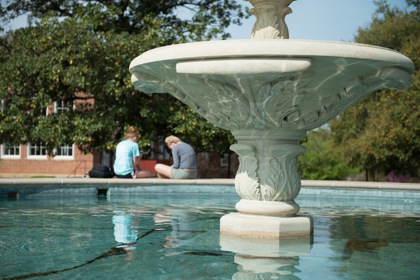 Two students sitting at the TWU fountain