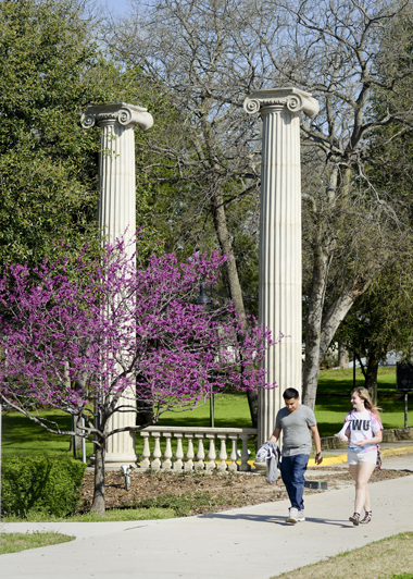 Students walking next to TWU columns