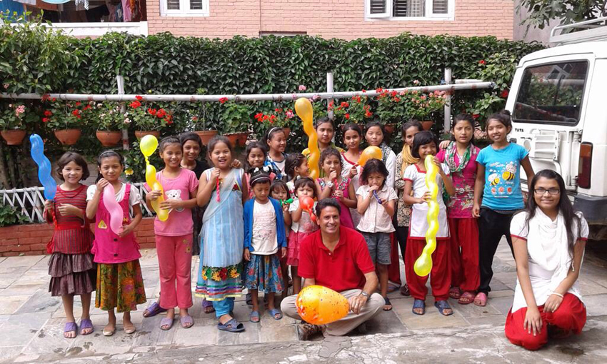 Ronald S. Palomares-Fernandez, Ph.D., (seated, front center) works with children at an orphanage in Nepal.