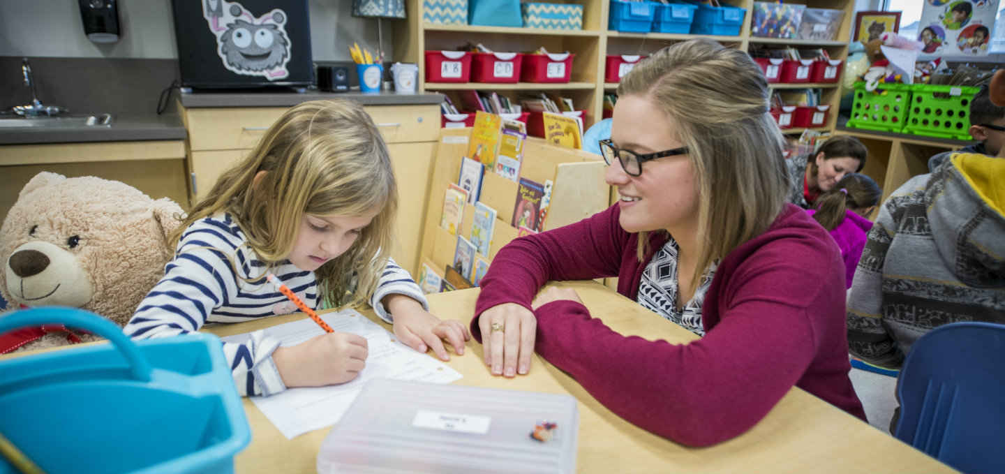 Student teacher assist a young girl with reading homework.