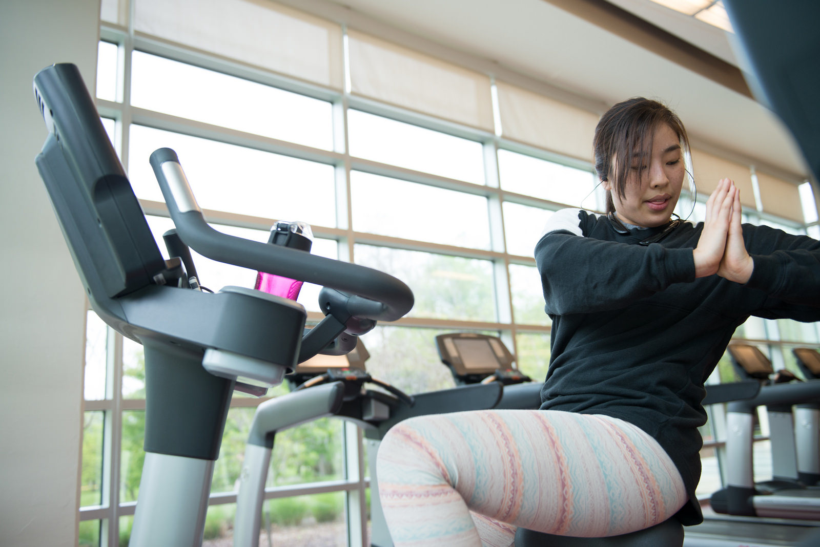 Woman at a stationary bike stretching.