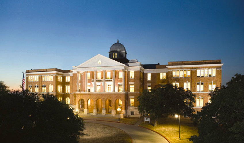 The outside of Old Main Building at Texas Woman's University at dusk.