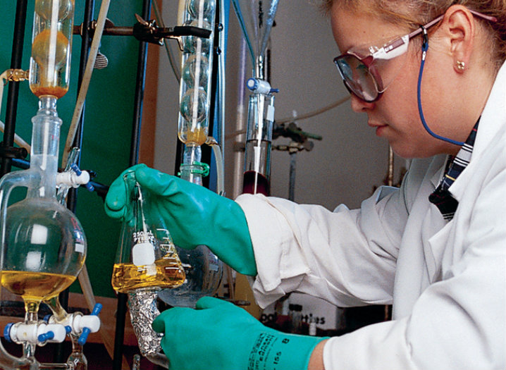 Female wearing a lab coat, safety goggles and gloves, while working in a lab.