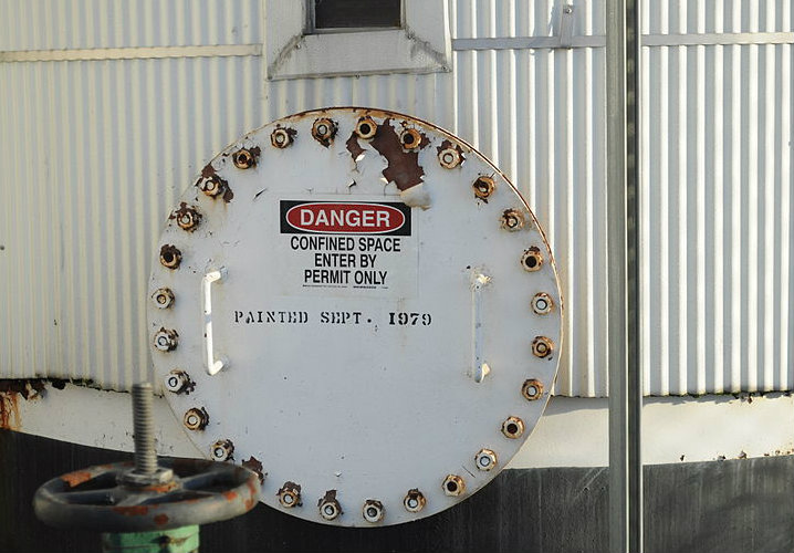 "Warning sign on a silo door says ""Danger confined space enter by permit only""."