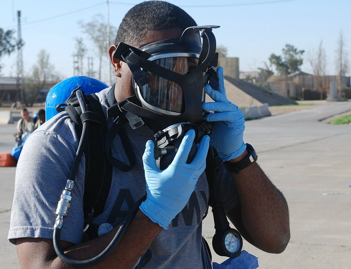 A male putting on a respirator.