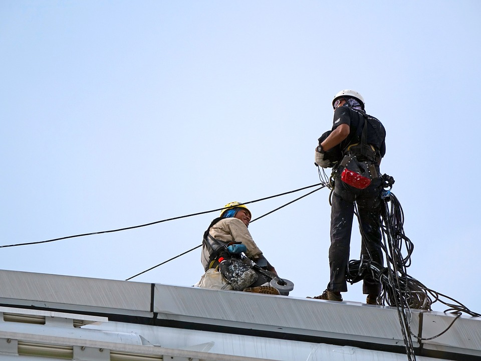 Two guys on top of a building using personal fall arrest systems.