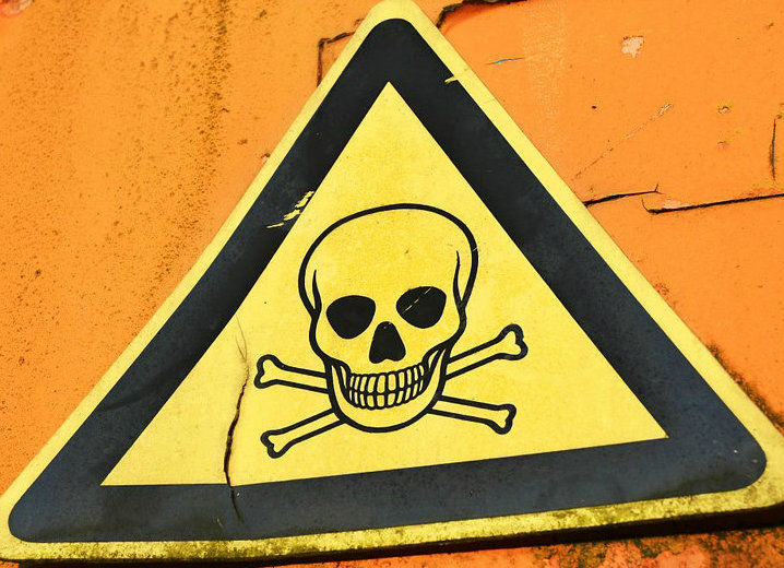 Yellow triangle warning sign with skull and cross bones.