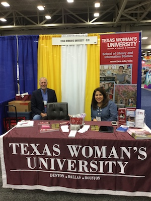 man and woman sitting and smiling at table draped with banner reading Texas Woman's University