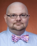 A photo of a man with glasses and a pink bowtie.