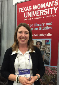 A woman smiling in front of a Texas Woman's University banner.