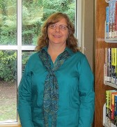A photo of Sue Ridnour. She has blonde hair and is wearing a teal blouse.