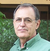 A photo of a man with glasses and wearing a green collared shirt.