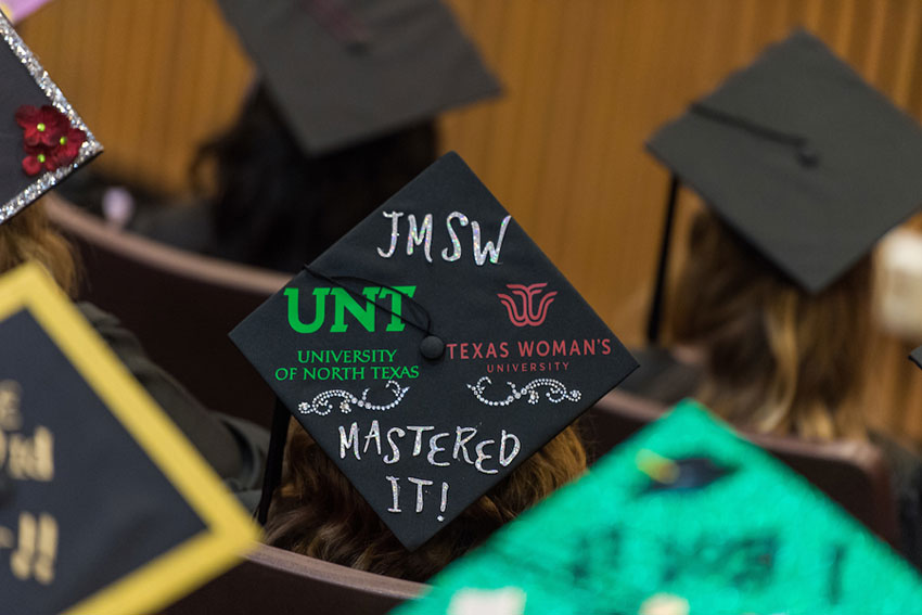 A graduate cap decorated with both university logos and
